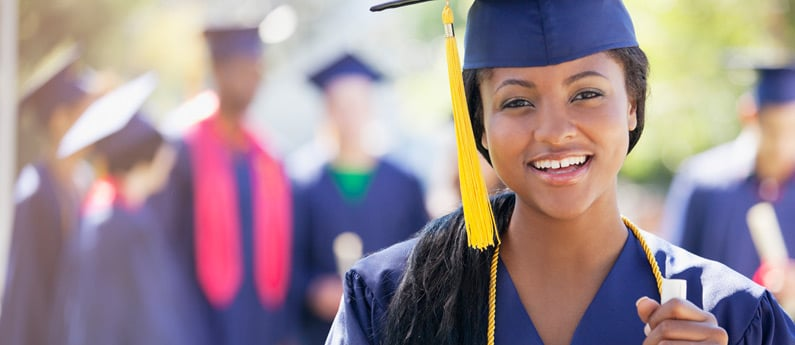 Close up of a graduating student wearing a graduation cap and gown