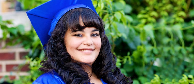 Close up of a graduating student in a graduation cap and gown.
