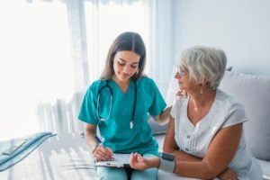Medical Assistant Working With Older Woman