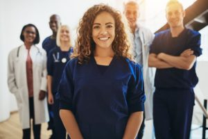 Medical Assistant Stands In Front of Coworkers