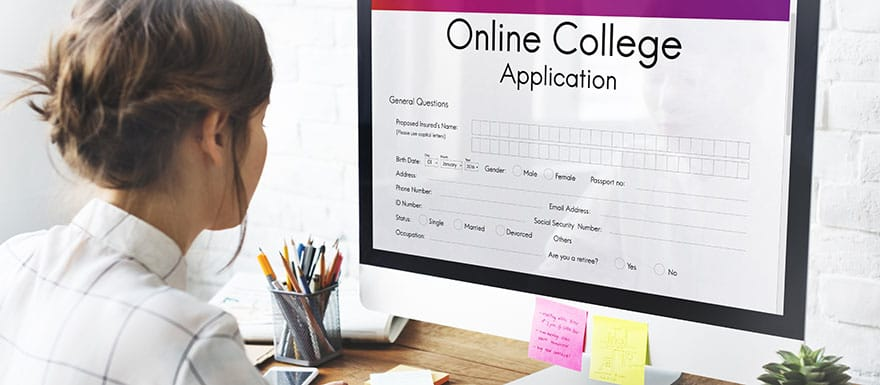 Woman filling out an Online College Application on a desktop computer.